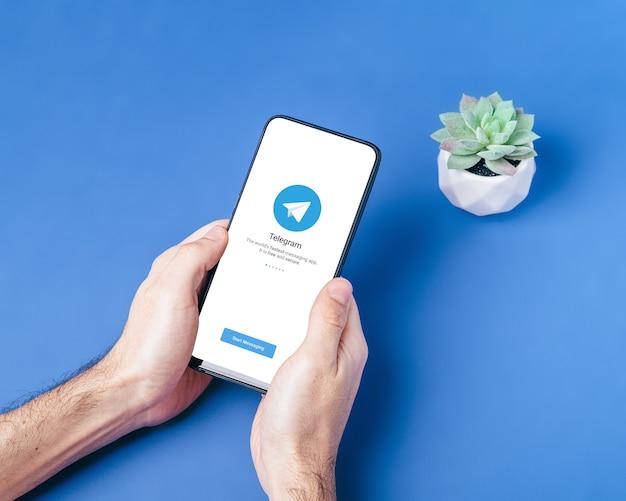 Telegram-toepassingspictogram op het smartphonescherm. online beveiligd sociaal medianetwerk. blauw oppervlak