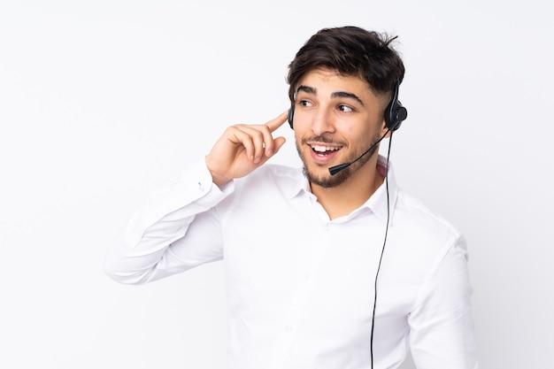 Telemarketeer arabische man aan het werk met een headset op wit wordt geïsoleerd