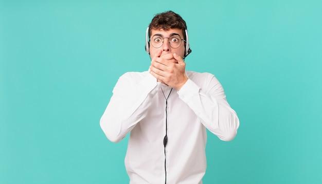 Telemarketeer bedekt mond met handen met een geschokte, verbaasde uitdrukking, houdt een geheim of zegt oeps