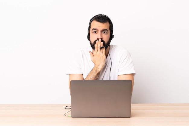 Telemarketeer blanke man aan het werk met een headset en met een laptop die de mond bedekt met de hand.