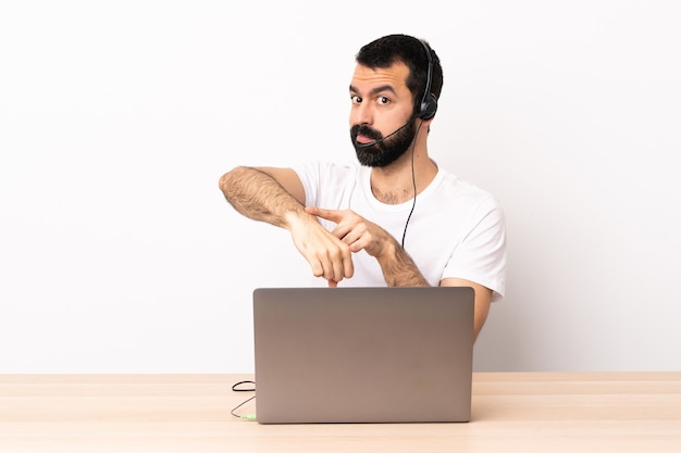 Telemarketeer blanke man aan het werk met een headset en met een laptop die het gebaar maakt om te laat te zijn.