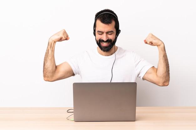 Telemarketeer blanke man aan het werk met een headset en met laptop doet sterk gebaar.