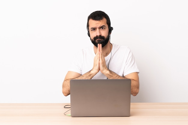Telemarketeer blanke man aan het werk met een headset en met laptop houdt palm bij elkaar. persoon vraagt iets.