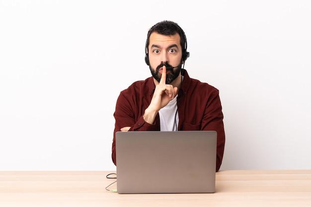 Telemarketeer blanke man aan het werk met een headset en met laptop met een teken van stilte gebaar vinger in de mond steken.