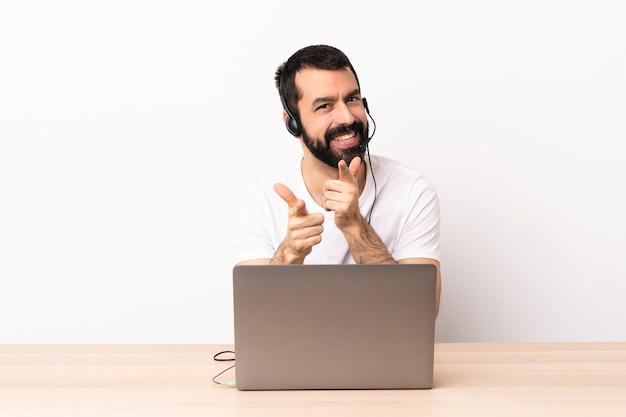 Telemarketeer blanke man aan het werk met een headset en met laptop naar de voorkant wijzen en glimlachen
