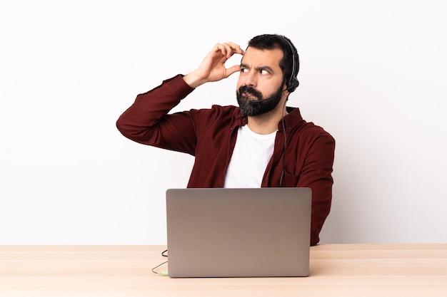 Telemarketeer blanke man aan het werk met een headset en met laptop twijfels terwijl hoofd krabben.