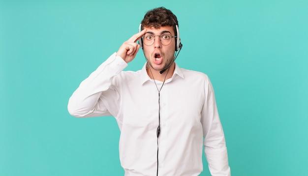 Telemarketeer die verrast, met open mond, geschokt kijkt en een nieuwe gedachte, idee of concept realiseert
