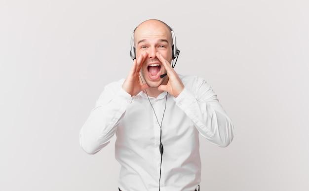 Telemarketeer die zich gelukkig, opgewonden en positief voelt, een grote schreeuw geeft met de handen naast de mond, roept