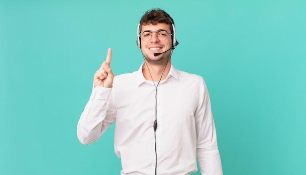 Telemarketeer lacht en ziet er vriendelijk uit, toont nummer één of eerste met hand naar voren, aftellend