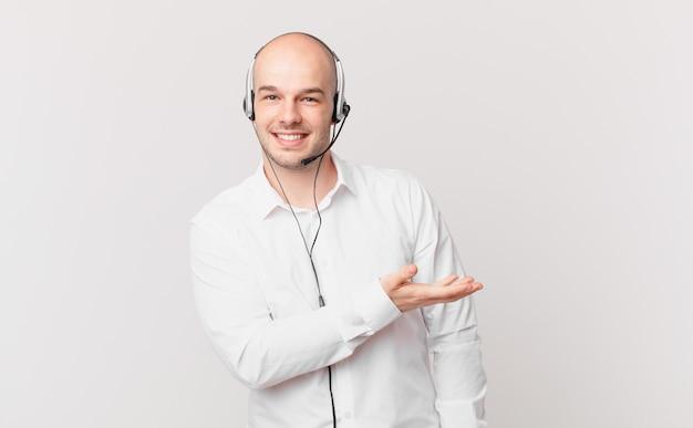 Telemarketeer lacht vrolijk en voelt zich gelukkig en toont een concept in kopieerruimte met handpalm