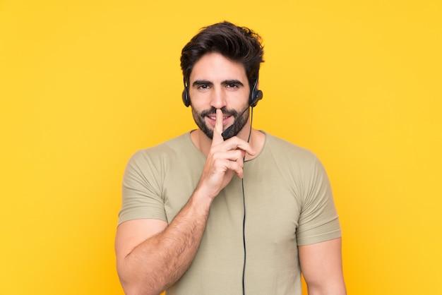 Telemarketeer man aan het werk met een headset over geïsoleerde gele muur doet stilte gebaar