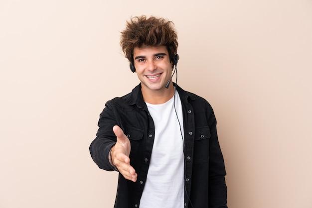 Telemarketeer man aan het werk met een headset over geïsoleerde muur handshaking na goede deal