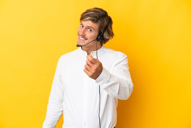 Telemarketeer man aan het werk met een hoofdtelefoon geïsoleerd op geel geld gebaar maken