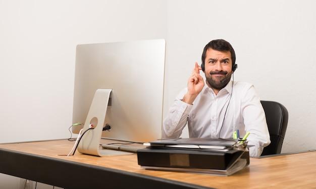 Telemarketeer man in een kantoor met vingers kruisen en het beste wensen