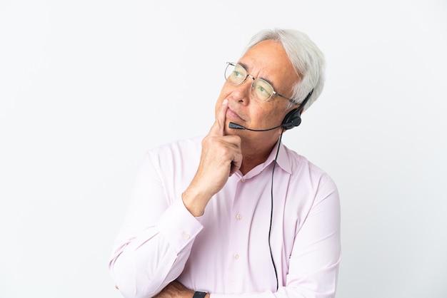 Telemarketeer man van middelbare leeftijd die met een headset werkt, geïsoleerd en twijfelt terwijl hij omhoog kijkt