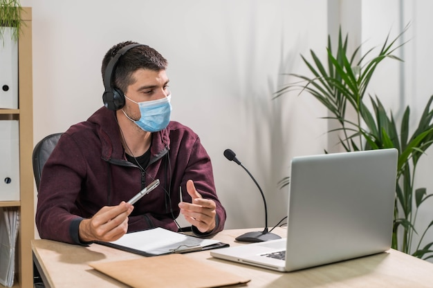 Telemarketeer of podcast man aan het werk met laptop en praten op een headset met gezichtsmasker op kantoor