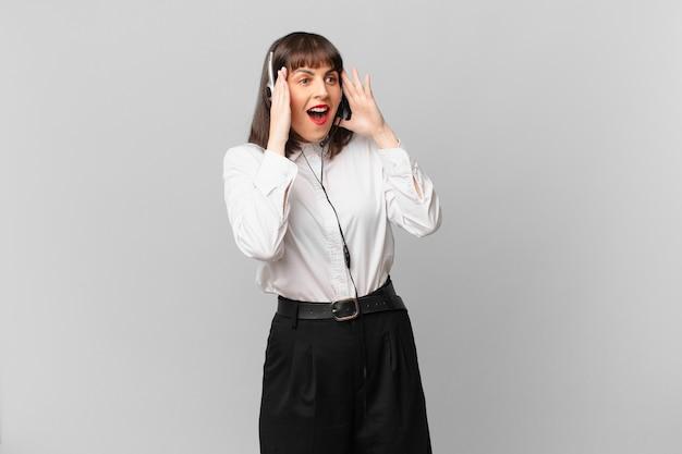 Telemarketeer-vrouw die zich gelukkig, opgewonden en verrast voelt, opzij kijkend met beide handen op het gezicht