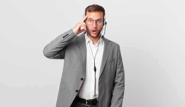 Telemarketeer zakenman die verrast kijkt en een nieuwe gedachte, idee of concept realiseert