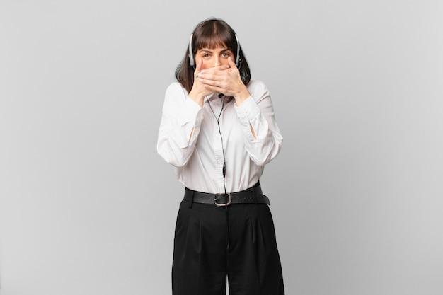 Telemarketeervrouw die mond bedekt met handen met een geschokte, verbaasde uitdrukking, een geheim houdt of oeps zegt