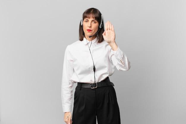 Telemarketeervrouw die serieus, streng, ontevreden en boos kijkt en een open palm toont die een stopgebaar maakt