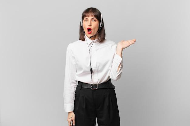 Telemarketeervrouw die verrast en geschokt kijkt, met open mond en een object vasthoudt met een open hand aan de zijkant