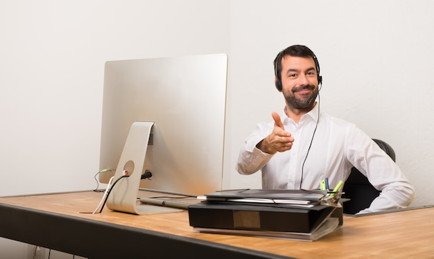 Telemarketer man in een kantoor handshaking na goede deal