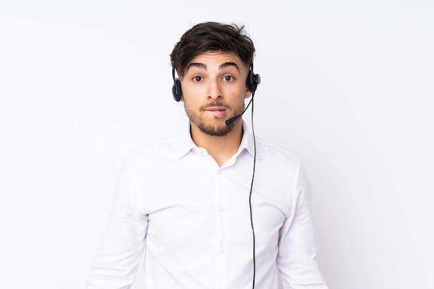 Telemarketermens die met een hoofdtelefoon werken die aan witte muur wordt geïsoleerd die twijfels heeft en met gezichtsuitdrukking verwart
