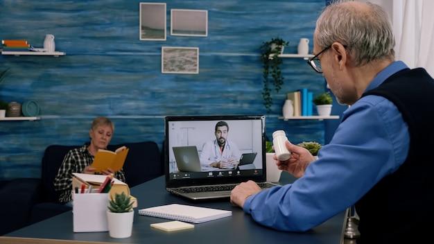 Telemedicine consult tijdens covid pandemie, man zit voor laptop in de keuken. zieke dame bespreekt tijdens virtueel consult over symptomen met flesje pillen