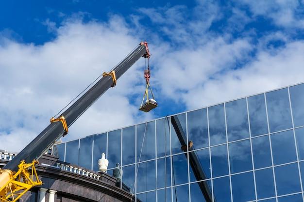 Telescopische giek van een bouwkraan heft de last tegen de spiegelwand van het gebouw