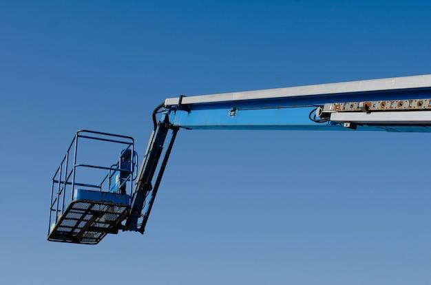 Telescopische hoogwerker opgewekt op blauwe hemelachtergrond afgeleverd