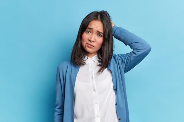 Teleurgesteld chagrijnig brunette jonge vrouw met oosterse uitstraling krassen hoofd frons gezicht kijkt ongelukkig camera draagt wit overhemd en blauwe trui vormt binnen. negatieve emoties concept