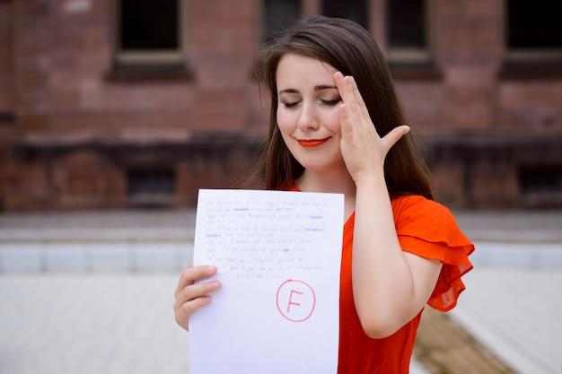 Teleurgesteld huilend studentenmeisje met mislukt testresultaat