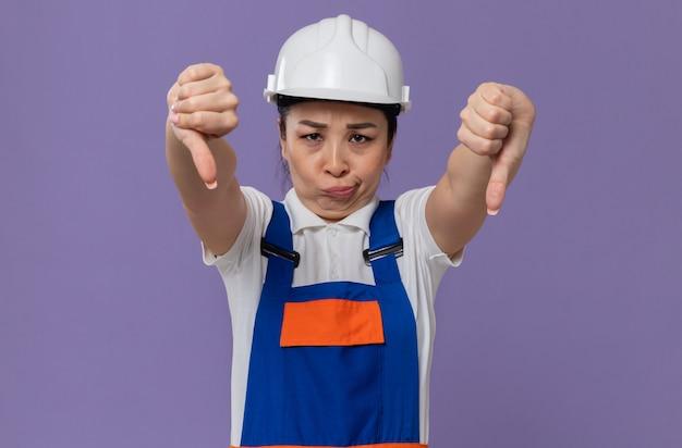 Teleurgesteld jong aziatisch bouwersmeisje met witte veiligheidshelm die naar beneden duimt