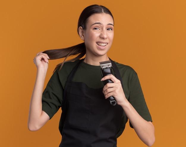 Teleurgesteld jong brunette kappersmeisje in uniform houdt tondeuses vast