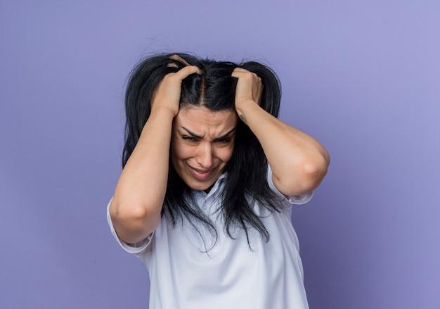 Teleurgesteld jong donkerbruin kaukasisch meisje houdt hoofd en kijkt geïsoleerd op paarse muur