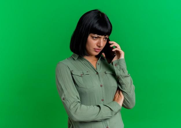 Teleurgesteld jong donkerbruin kaukasisch meisjesbesprekingen op telefoon die kant bekijken