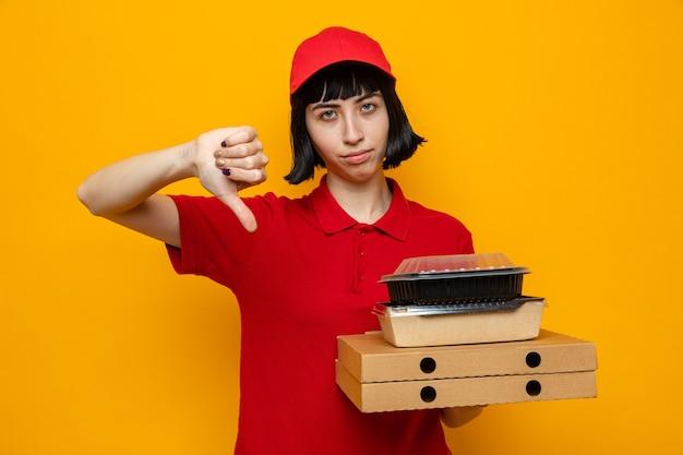 Teleurgesteld jong kaukasisch bezorgmeisje met voedselcontainers met verpakking op pizzadozen
