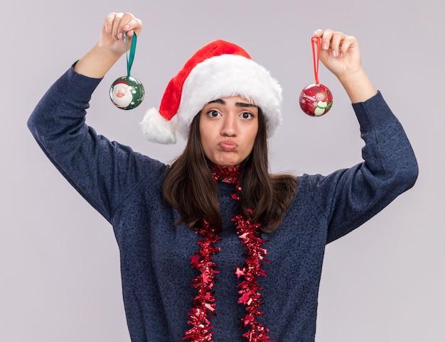 Teleurgesteld jong kaukasisch meisje met kerstmuts en slinger om nek met glazen bol ornamenten geïsoleerd op een witte muur met kopie ruimte