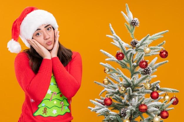 Teleurgesteld jong kaukasisch meisje met kerstmuts legt handen op gezicht naast kerstboom geïsoleerd op een oranje achtergrond met kopie ruimte
