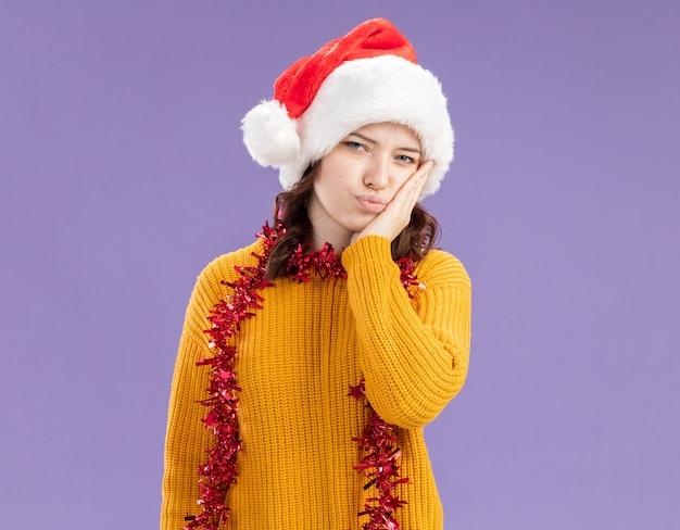 Teleurgesteld jong slavisch meisje met kerstmuts en met slinger om nek legt hand op gezicht geïsoleerd op paarse muur met kopieerruimte