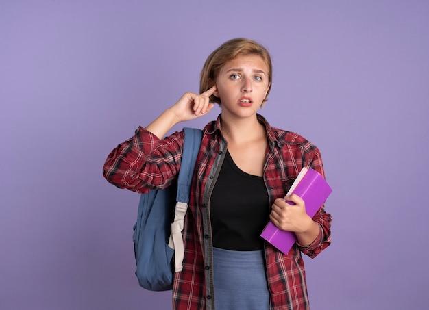 Teleurgesteld jong slavisch studentenmeisje dat rugzak draagt, houdt boek vast en notitieboekje sluit oor met vinger