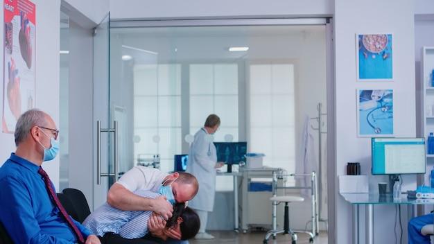 Teleurgesteld jong stel in de wachtruimte van het ziekenhuis van de dokter ongunstig slecht nieuws tijdens de uitbraak van het coronavirus. medic die gezichtsmasker draagt tegen infectie met covid-19.