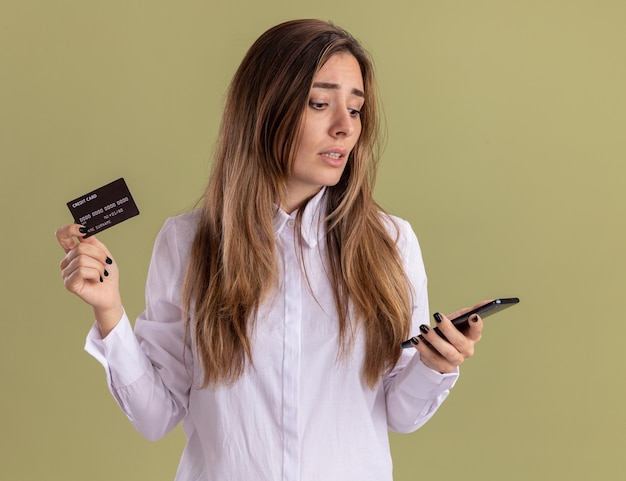 Teleurgesteld jong, vrij kaukasisch meisje heeft een creditcard en kijkt naar de telefoon