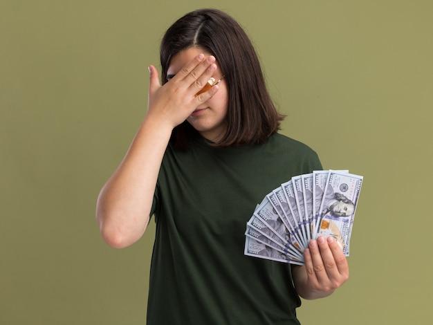 Teleurgesteld jong, vrij kaukasisch meisje in zonnebril legt hand op gezicht en houdt geld vast