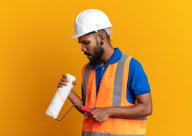 Teleurgesteld jonge afro-amerikaanse bouwer man in uniform met veiligheidshelm houden en kijken naar verfroller geïsoleerd op oranje achtergrond met kopie ruimte