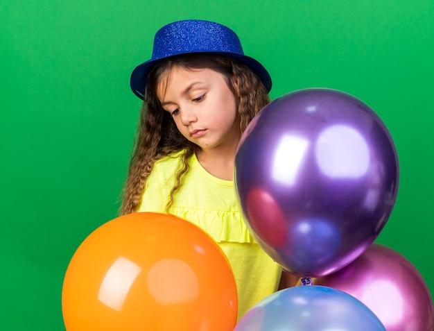 Teleurgesteld klein kaukasisch meisje met blauwe feestmuts met helium ballonnen en neerkijkt geïsoleerd op groene muur met kopie ruimte
