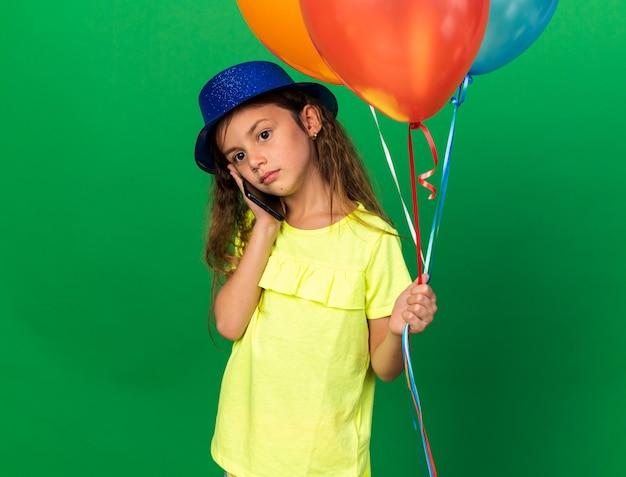 Teleurgesteld klein kaukasisch meisje met blauwe feestmuts met helium ballonnen en praten over telefoon geïsoleerd op groene muur met kopie ruimte