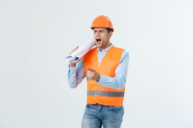 Teleurgesteld knappe ingenieur dragen oranje vest en jeans met helm, geïsoleerd op een witte achtergrond.