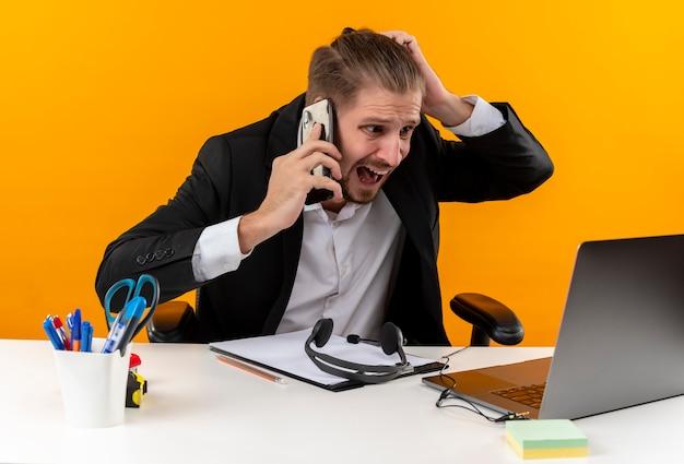 Teleurgesteld knappe zakenman in pak bezig met laptop praten op mobiele telefoon op zoek verward en ontevreden zittend aan tafel in het kantoor over oranje achtergrond