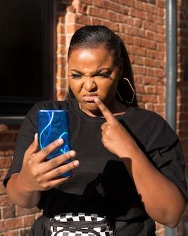 Teleurgesteld meisje kijkt naar haar telefoon